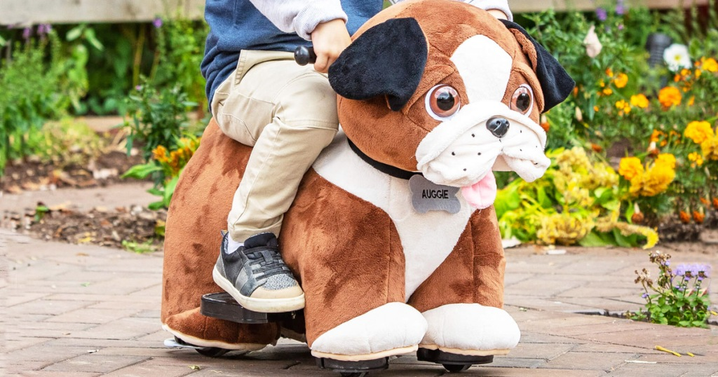 child riding on a plush brown and white dog ride-on toy in garden