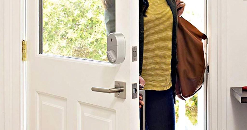woman in yellow sweater walking through front door with keyless smart lock installed on deadbolt