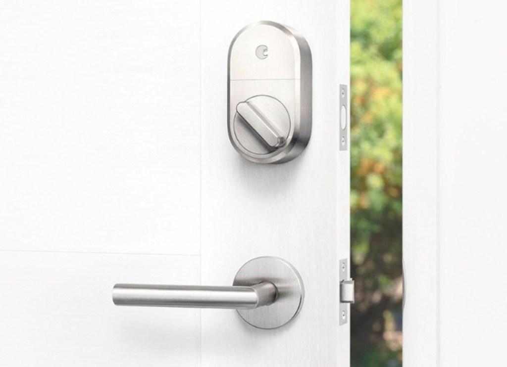 smart lock installed on deadbolt on inside of white door