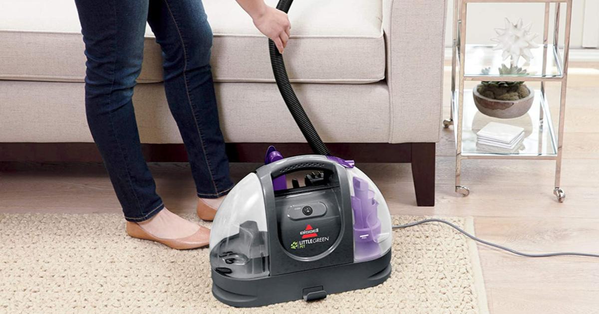 woman using pet vacuum cleaner in home