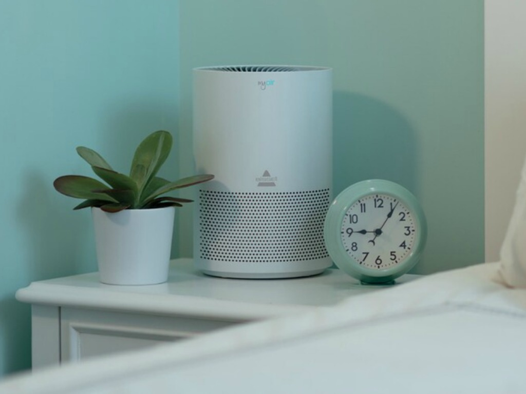 side table near bed with plant, clock and air purifier sitting on it