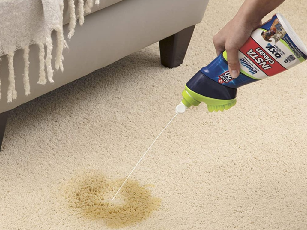 hand using pet cleaner on stained carpet in front of furniture