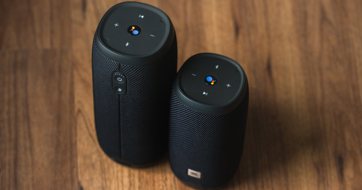 two different sized black bluetooth speakers standing on wooden table