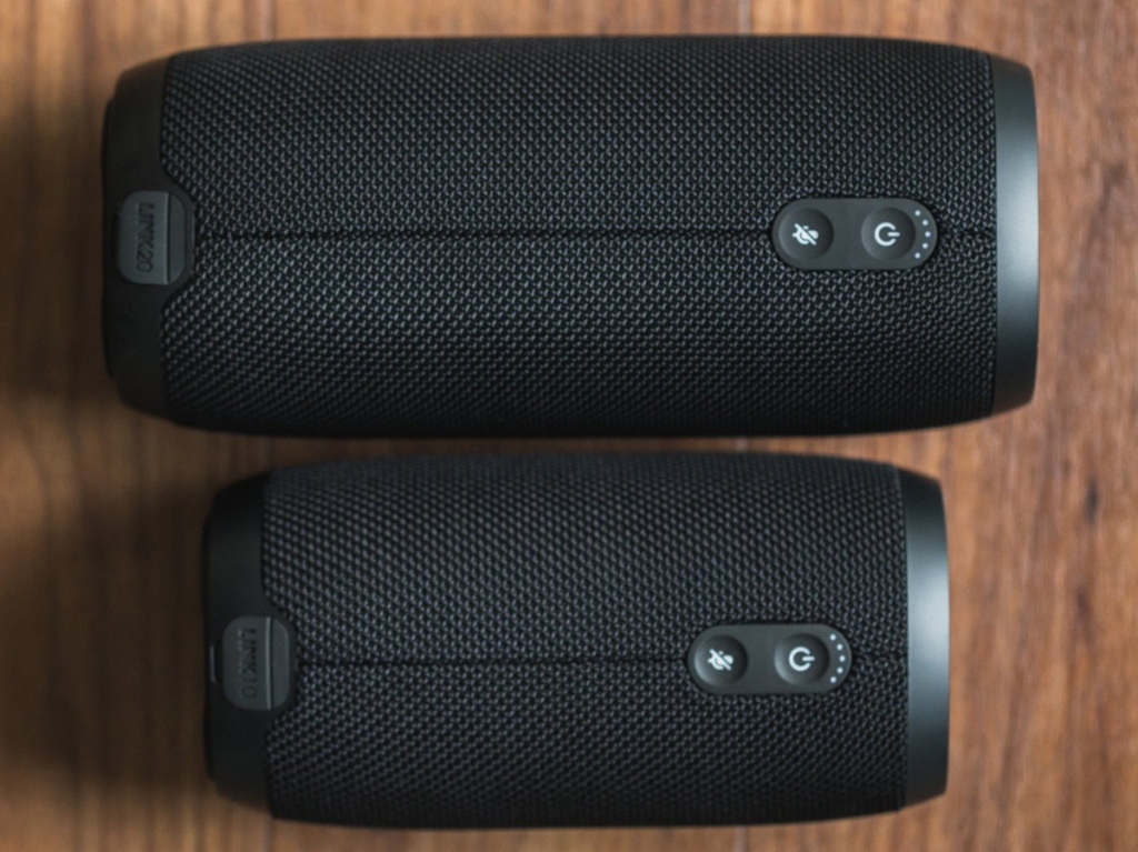 two different sized black bluetooth speakers laying on wooden table