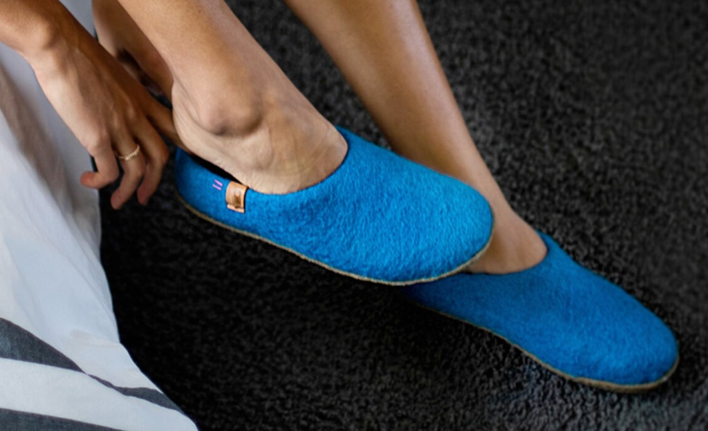 person putting on a pair of blue felted slip-on slippers