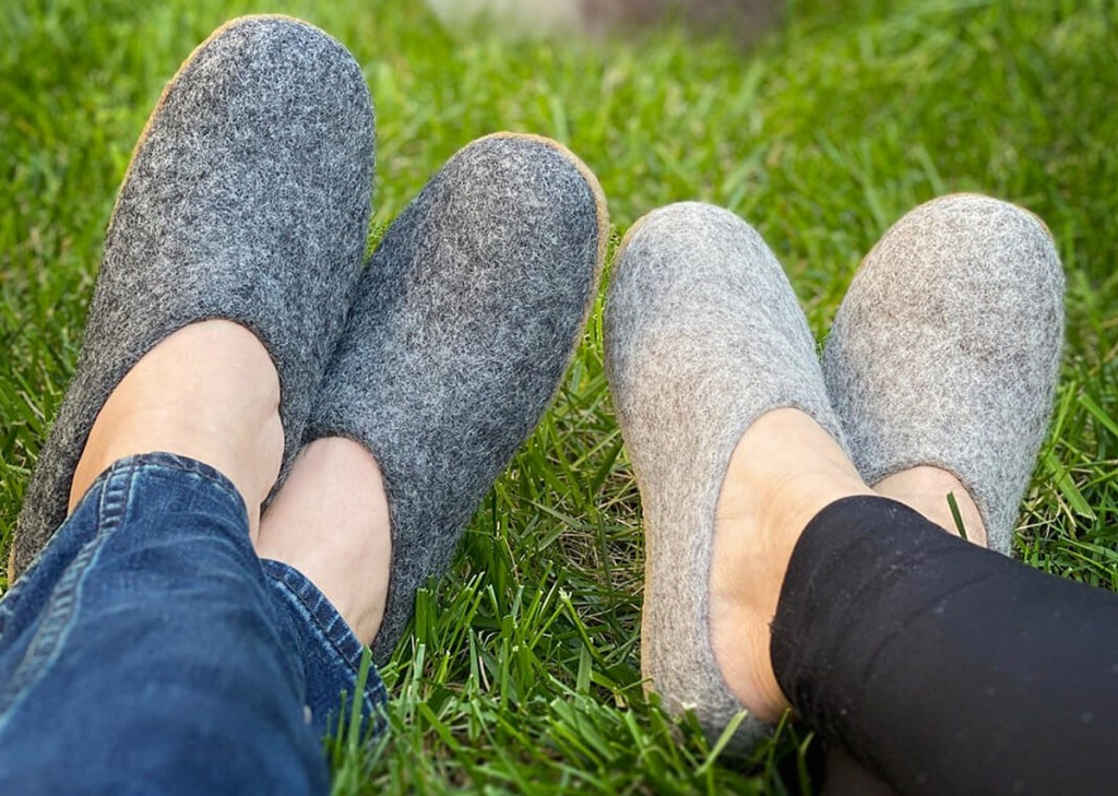 two people sitting in grass wearing grey felted slip-on slippers