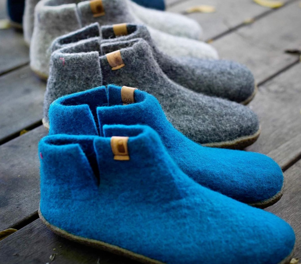 multiple pairs of felted slip-on booties in grey and blue colors on outdoor deck