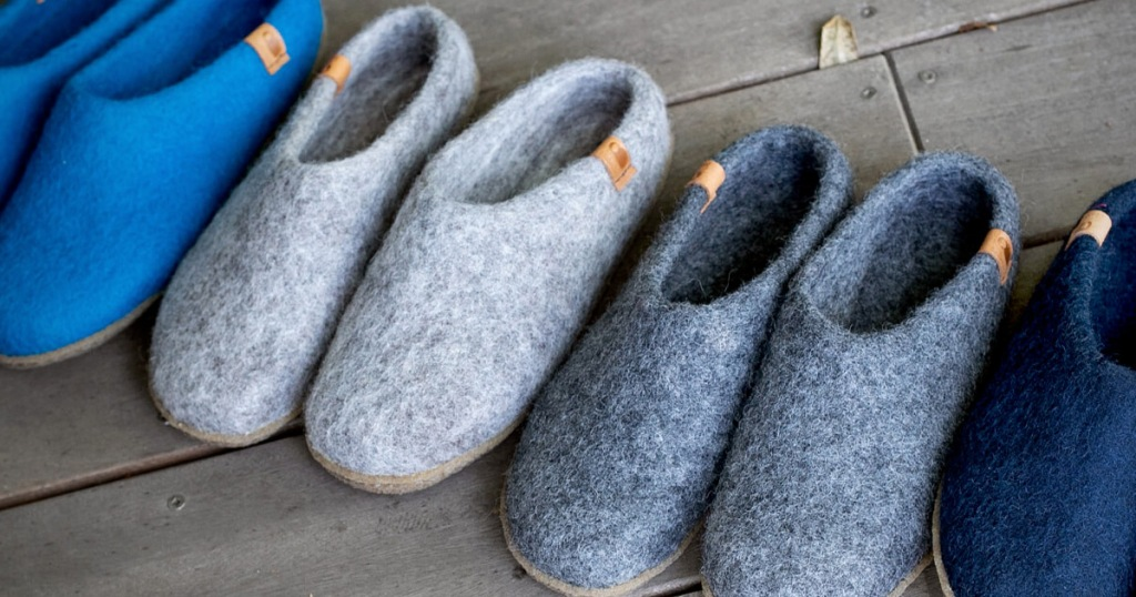 four pairs of felted slip-on slippers lined up on outdoor deck