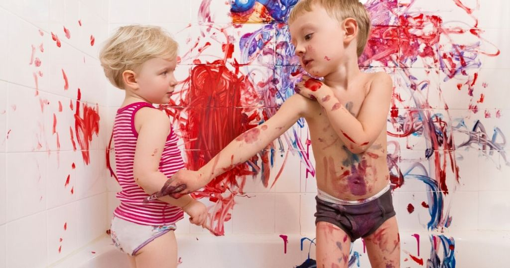Two kids painting in bathtub