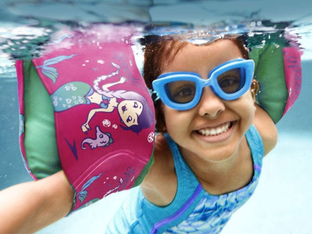 girl swimming under water with blue goggles and mermaid floaties