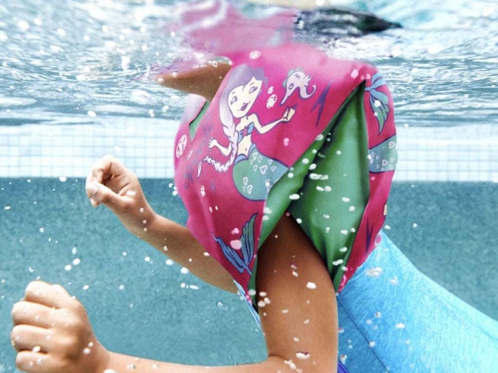 kids swimming in pool with mermaid arm floaties