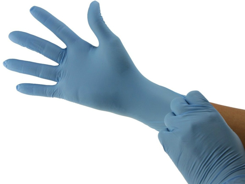 Woman pulling on a blue exam glove