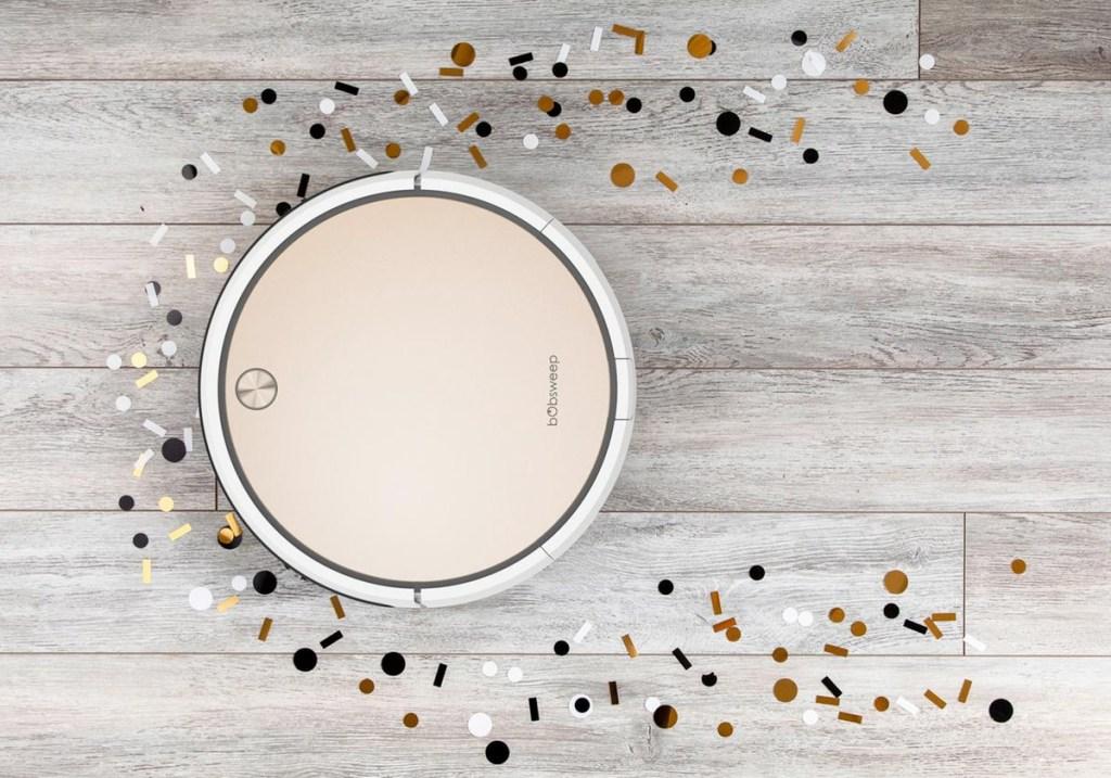 rose gold robotic vacuum picking up confetti glitter off hardwood floor