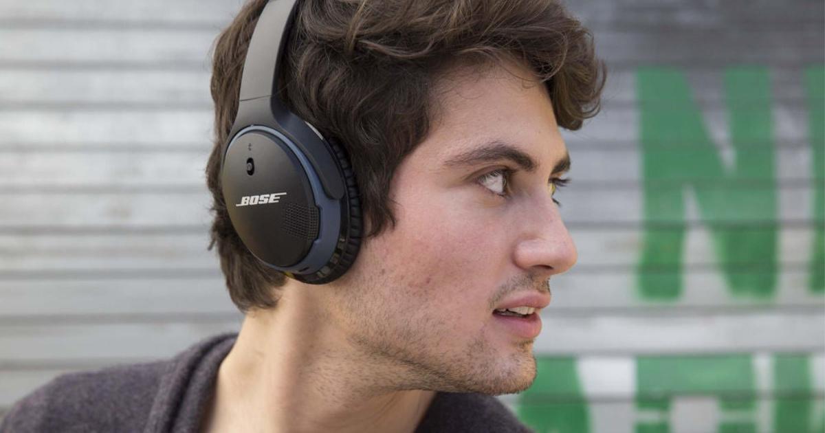 man wearing bose headphones turning head