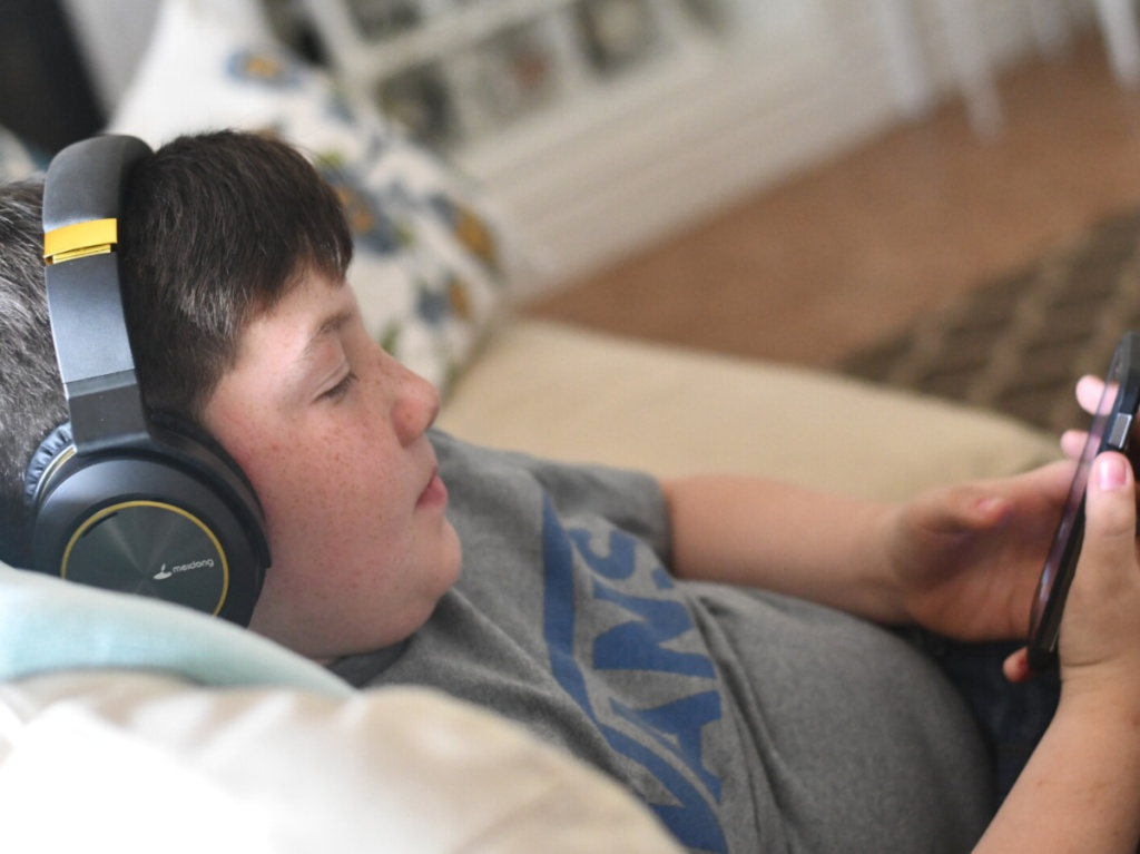 boy on couch with phone and headphones on