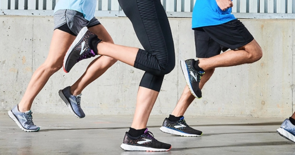 group of people in running shoes and athletic wear running on pavement