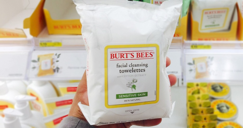 person holding up white pack of burts bees facial towelettes