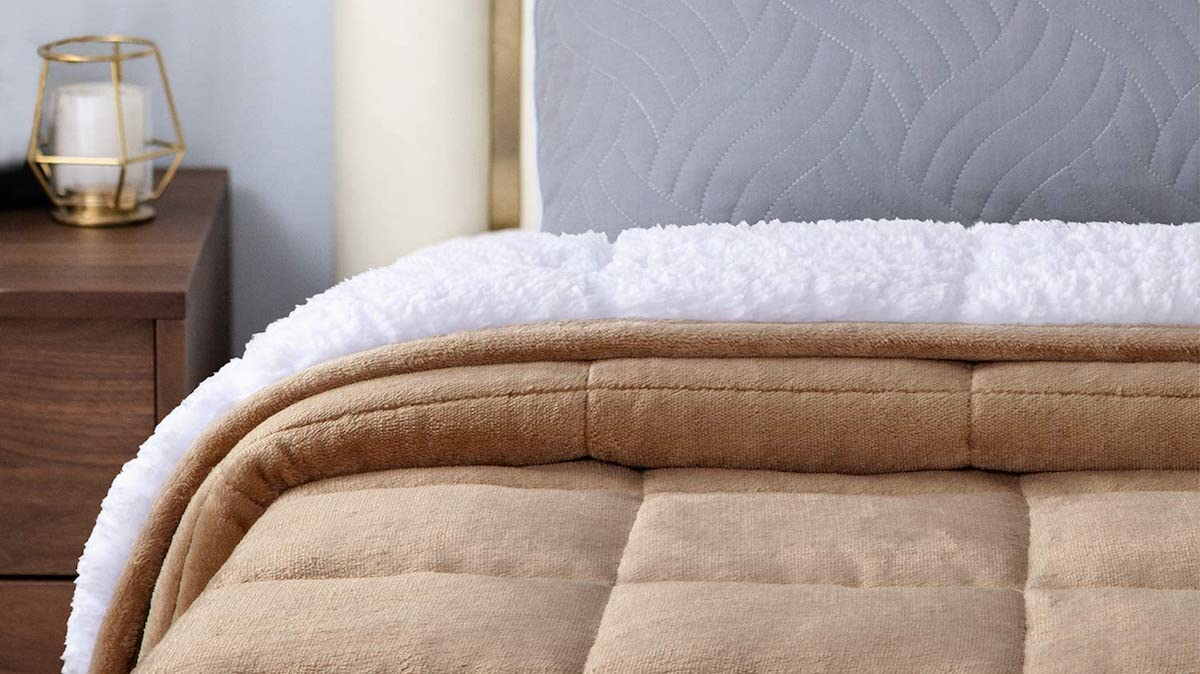 tan blanket with white sherpa side on a bed