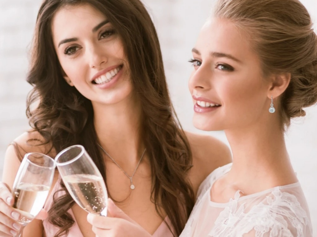Woman wearing drop earrings and doing cheers with champagne glasses