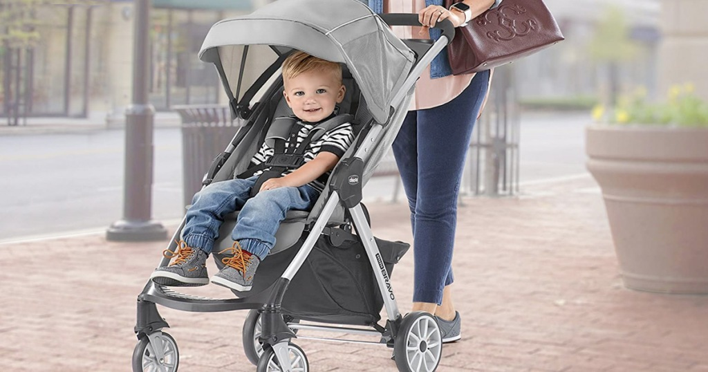 mother pushing child on sidewalk in grey and black baby stroller