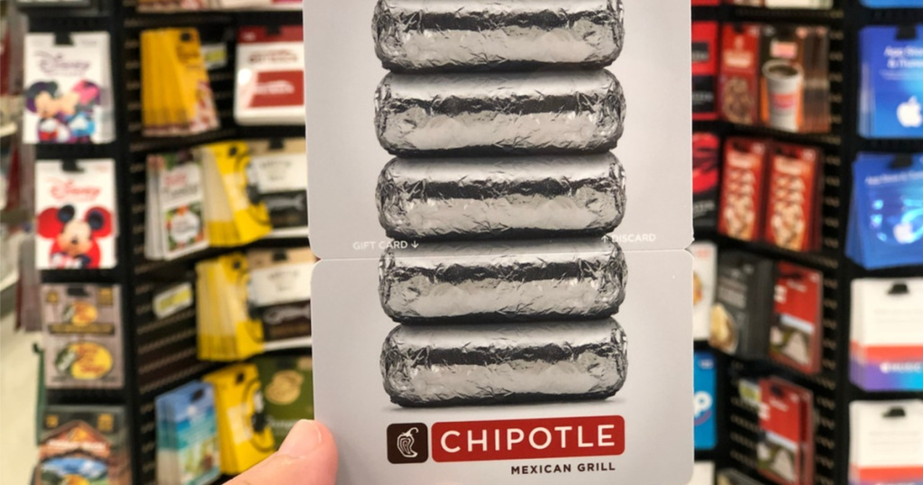 hand holding Chipotle gift card in front of gift card display in store
