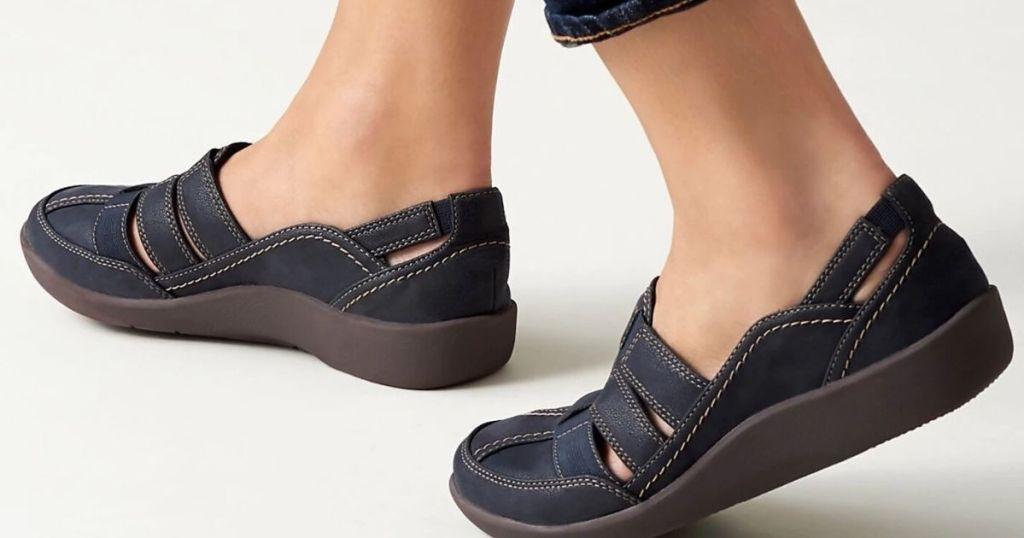woman's feet wearing flat sandal type shoes
