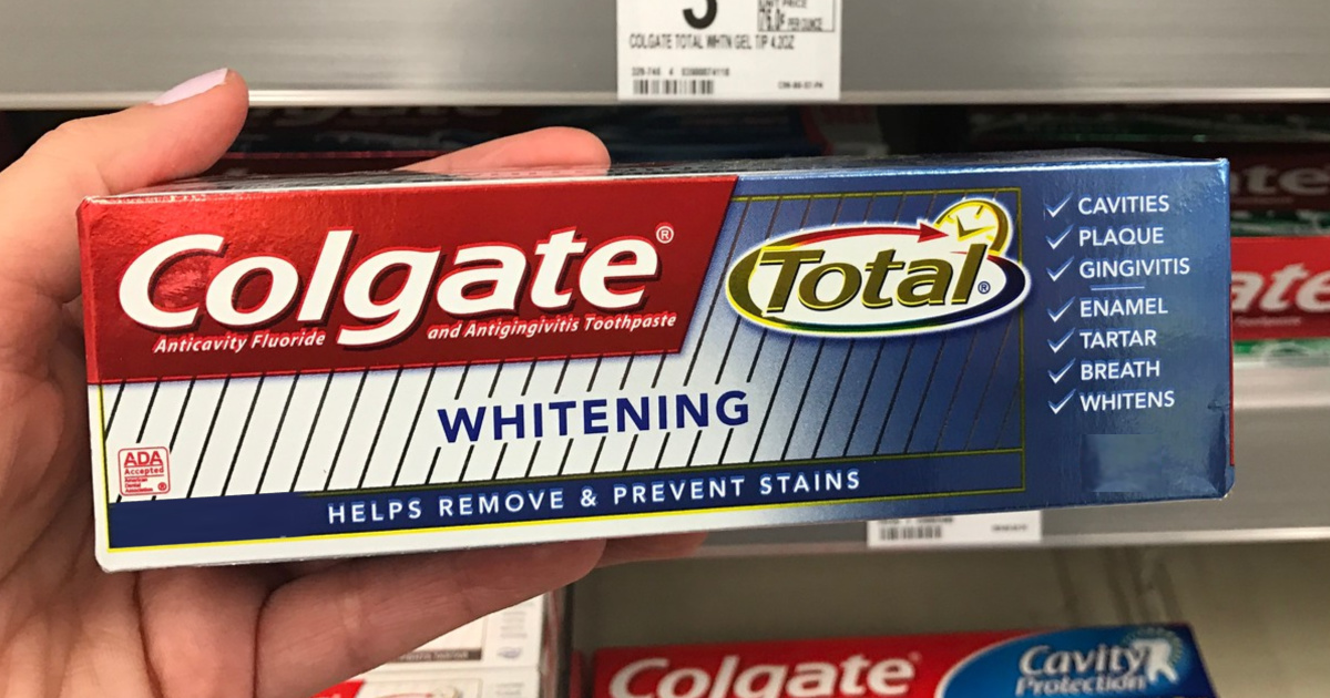 hand holding box of toothpaste in store aisle