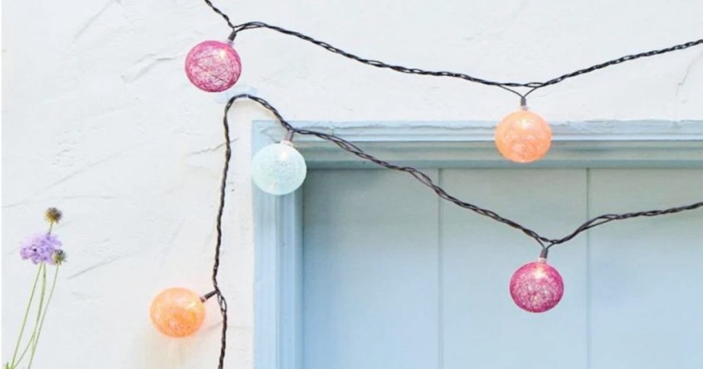 colorful orb shaped string lights strung across a blue door