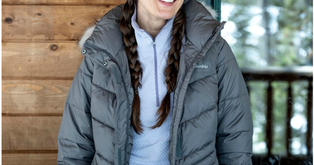woman standing in front of a cabin wearing a coat