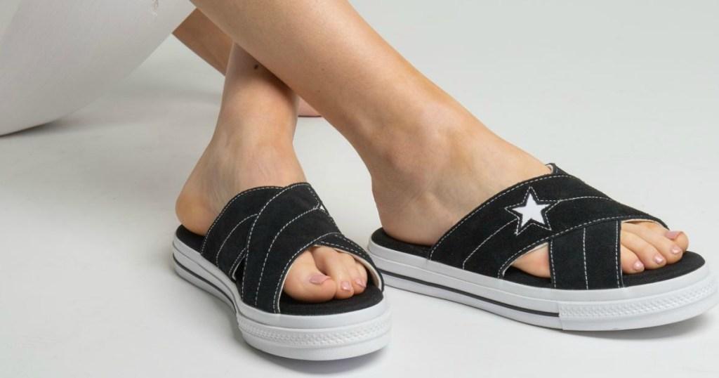 woman wearing black converse sandals