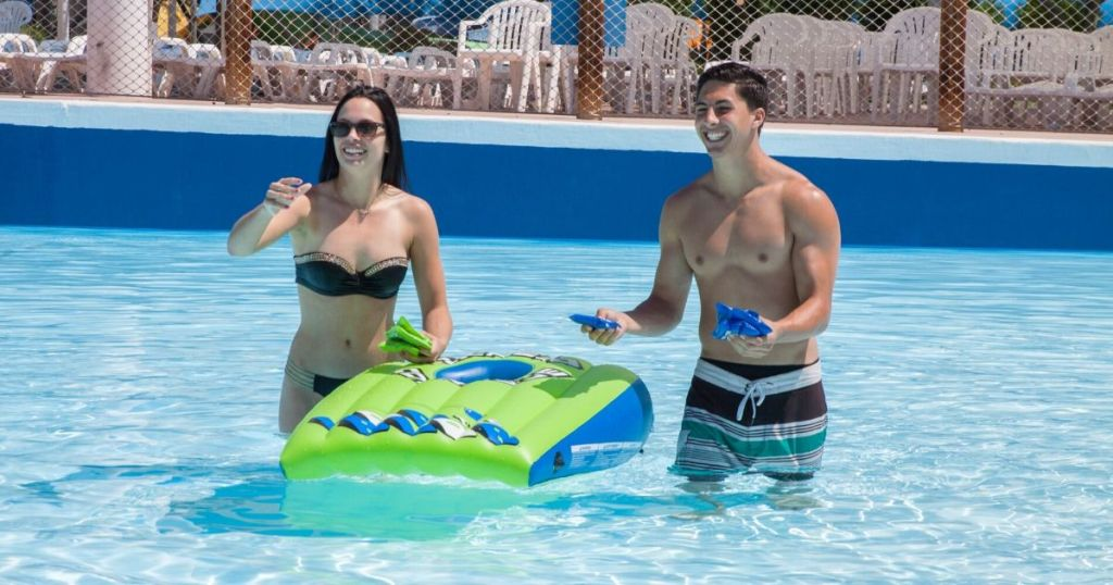 Woman and man in pool playing inflatable cornhole game
