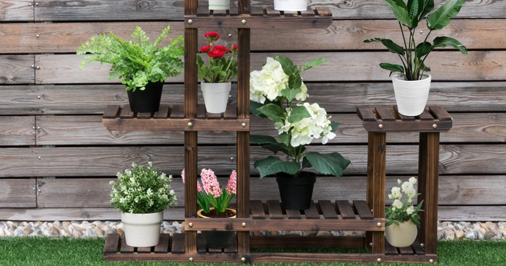 large wooden plant stand outside against fence with many plants on shelves