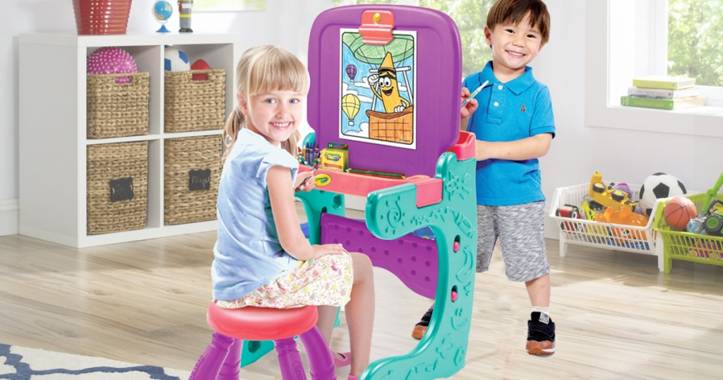 two kids coloring on an art easel in a playroom