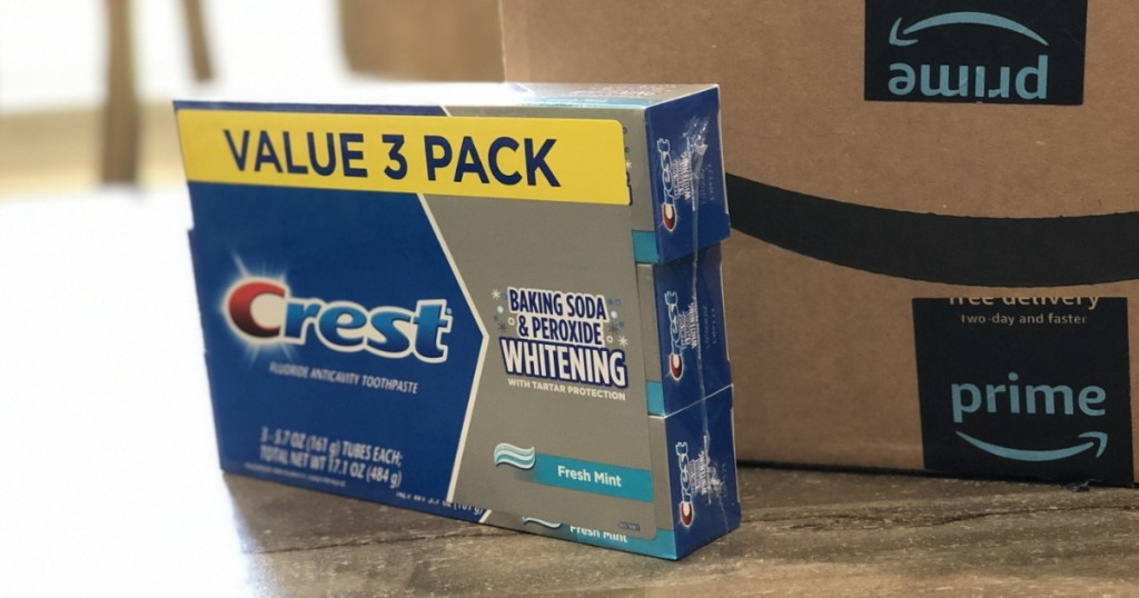 3 pack of Crest Toothpaste on table in front of Amazon box