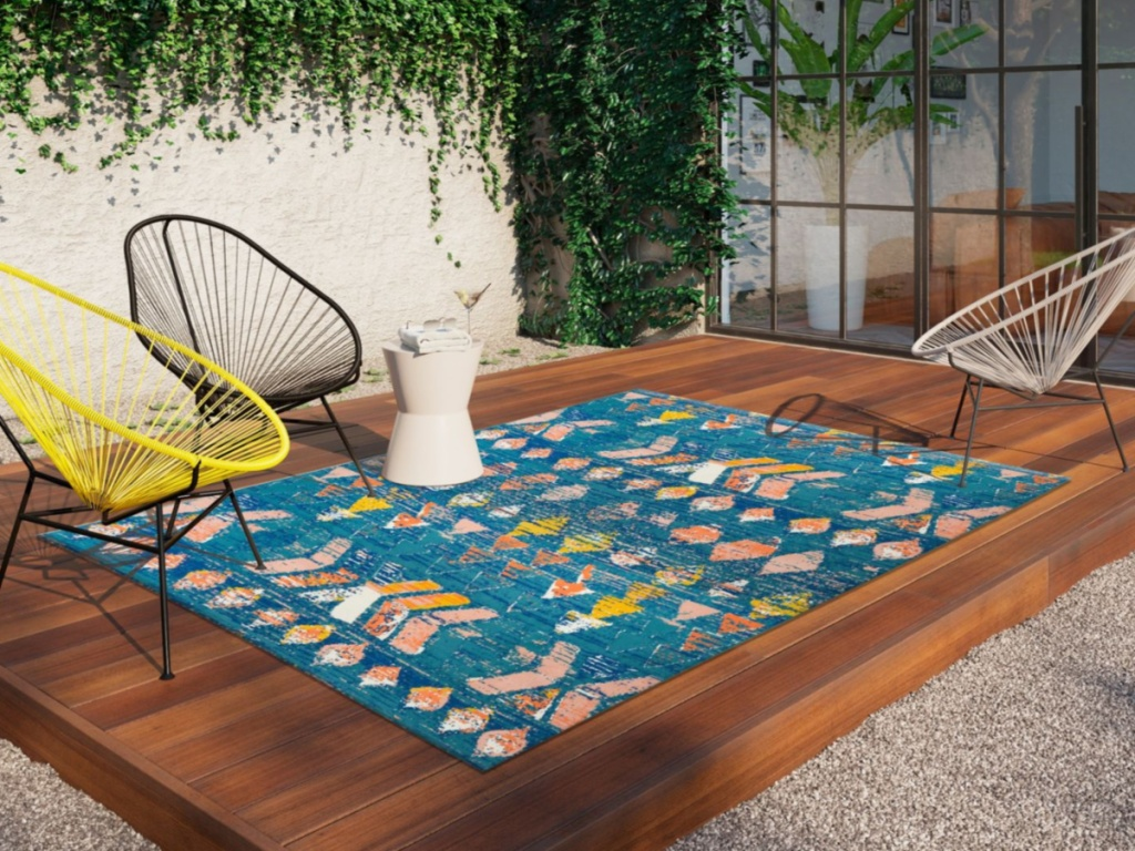 colorful blue rug on deck outdoors with black yellow and white chairs