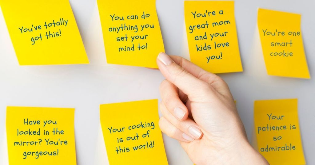 Hand grabbing an affirmation sticky note off the wall, next to other sticky notes