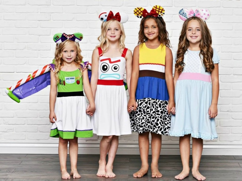 Four girls wearing a variety of Disney themed character dresses