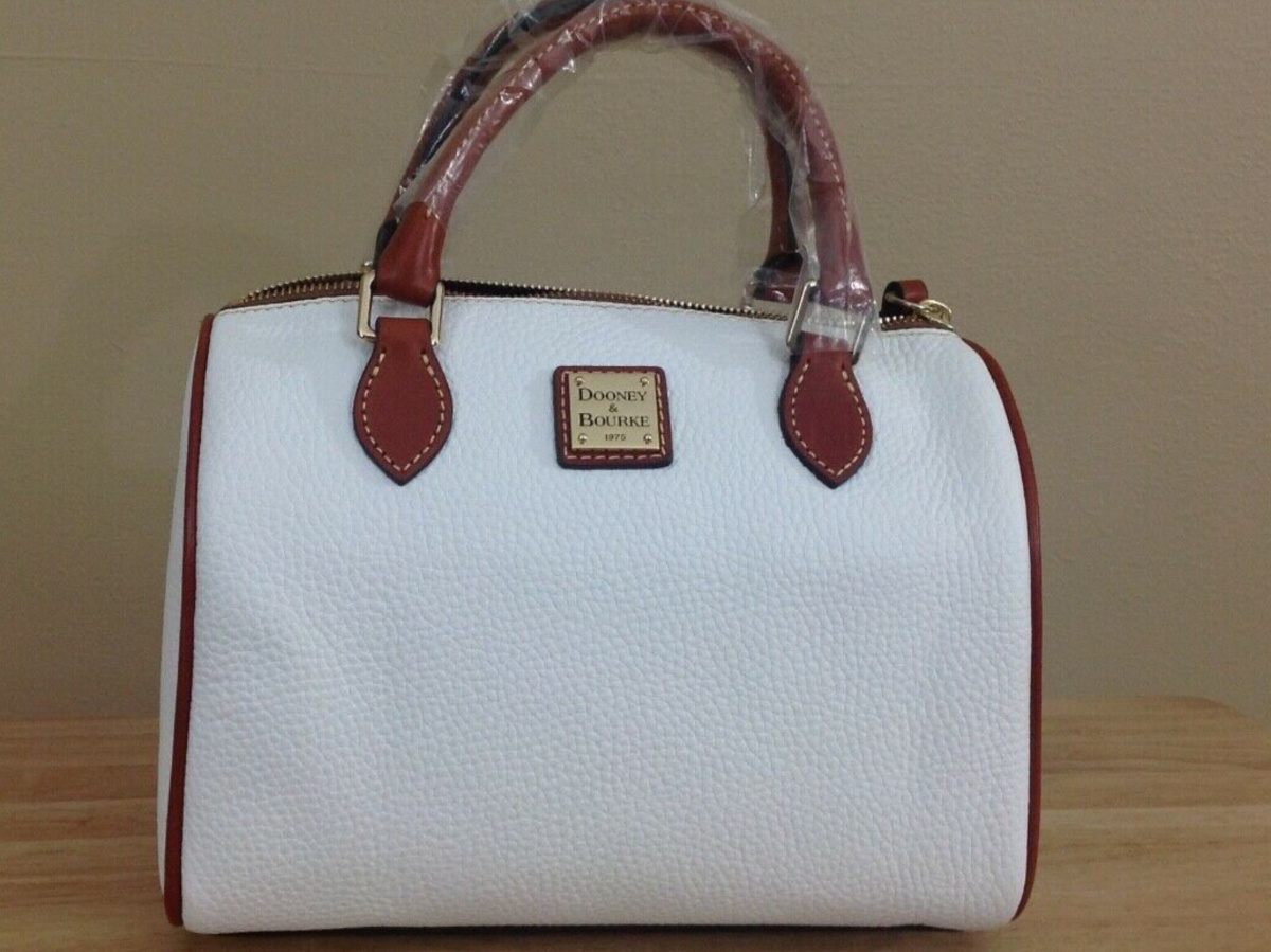 white and tan satchel on table