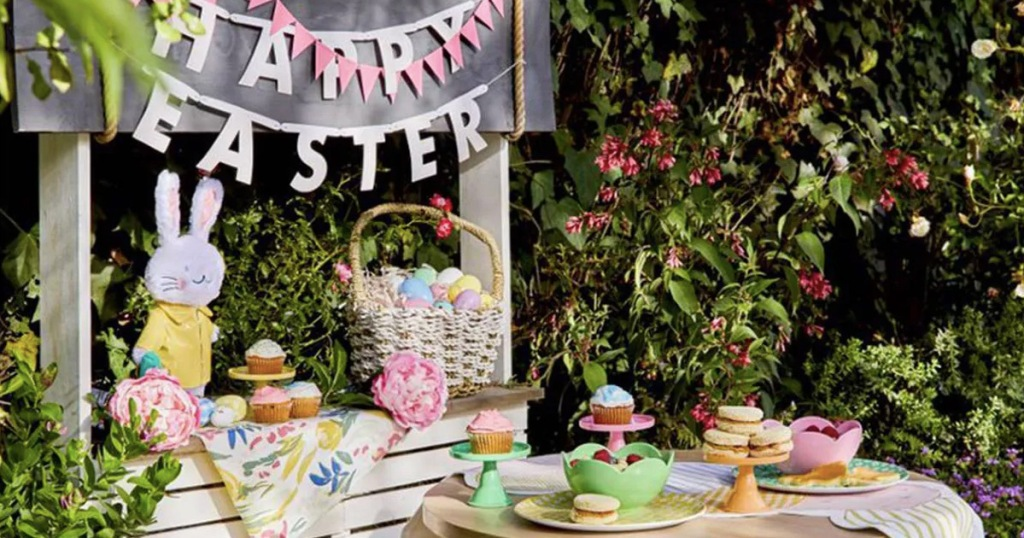 outdoor kids easter themed picnic with easter basket and colorful plates and cups