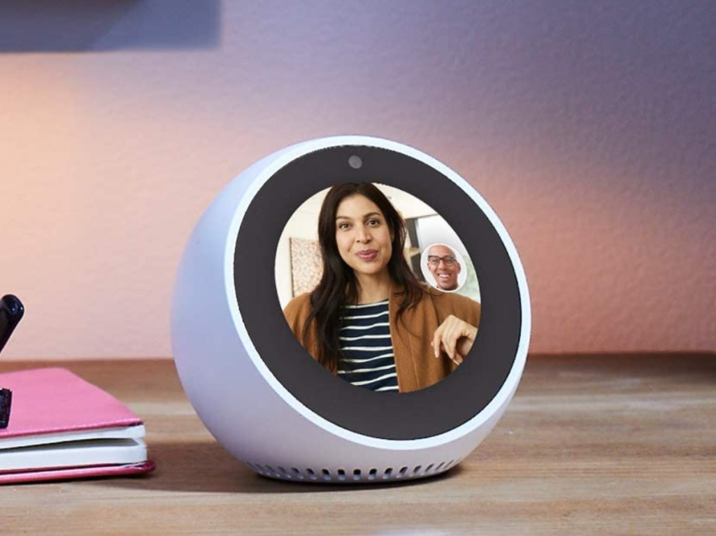 man video chatting with woman on smart alarm clock on desk