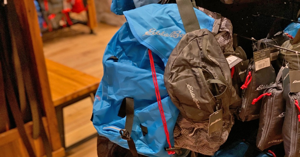 bright blue eddie bauer brand packable backpack hanging on store display