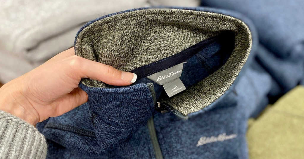 womans hand holding up a blue and grey eddie bauer brand sweater