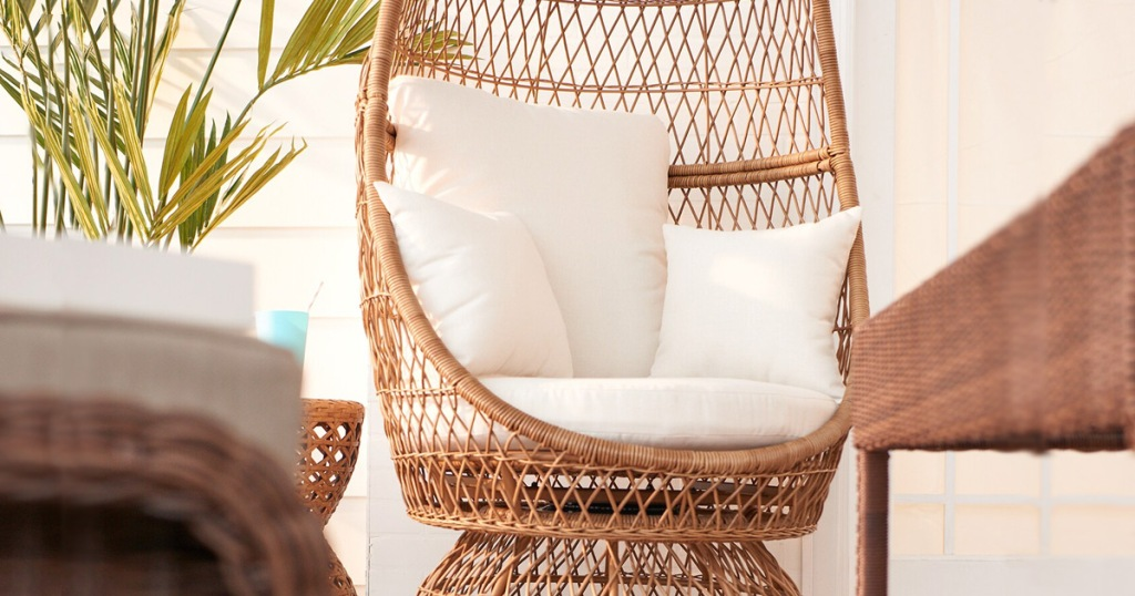 wicker egg chaped chair with white cushions in an outdoor patio space