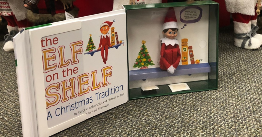 elf on the shelf book and doll in front of christmas tree in store