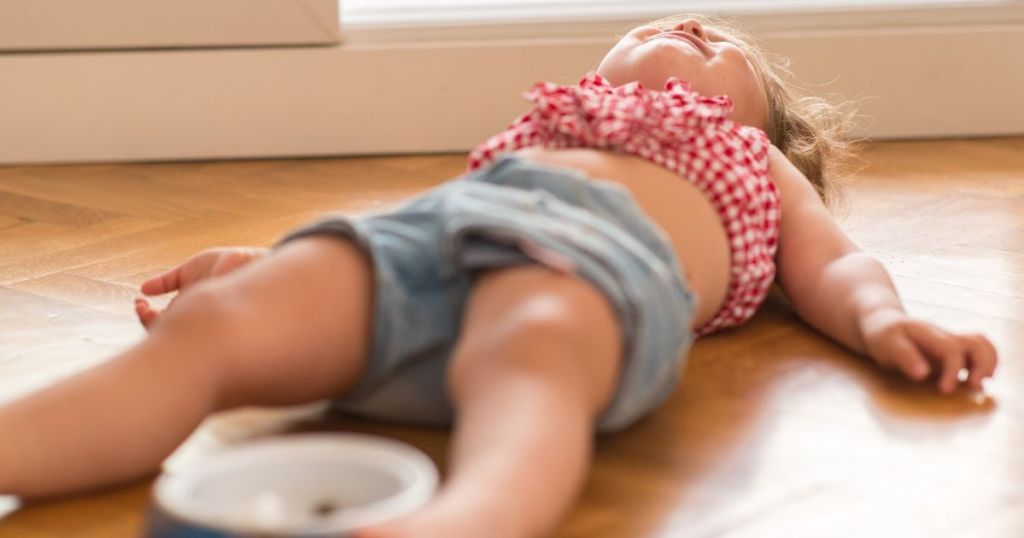 Child laying on floor, throwing a tantrum