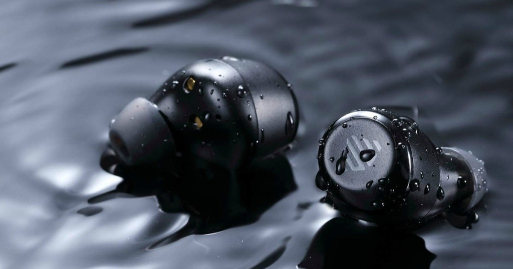 black earbuds on a watery surface