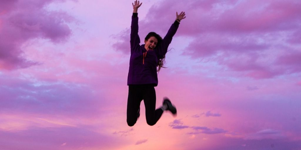 Energized woman jumping in the air with arms up