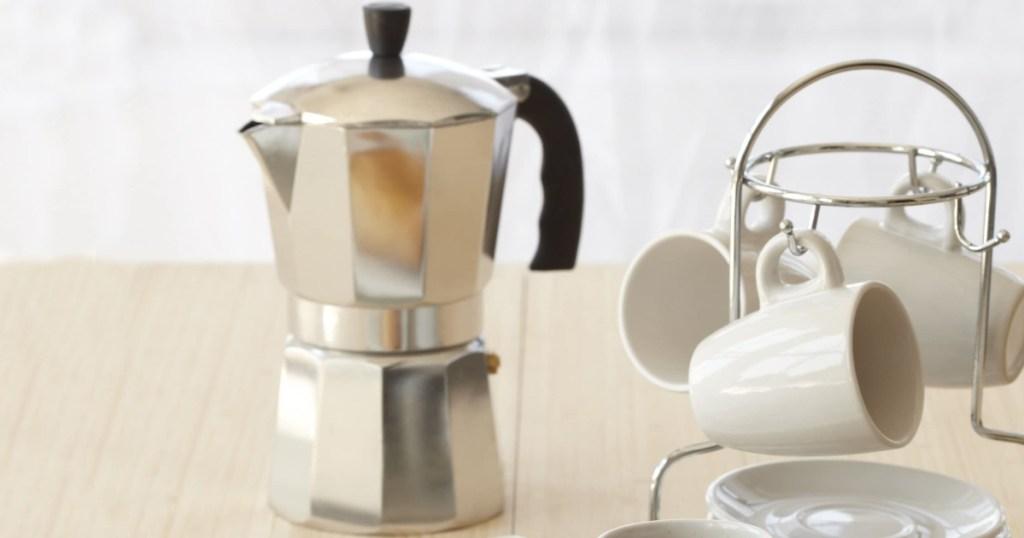 Silver Espresso Maker on counter top near mug and mug stand