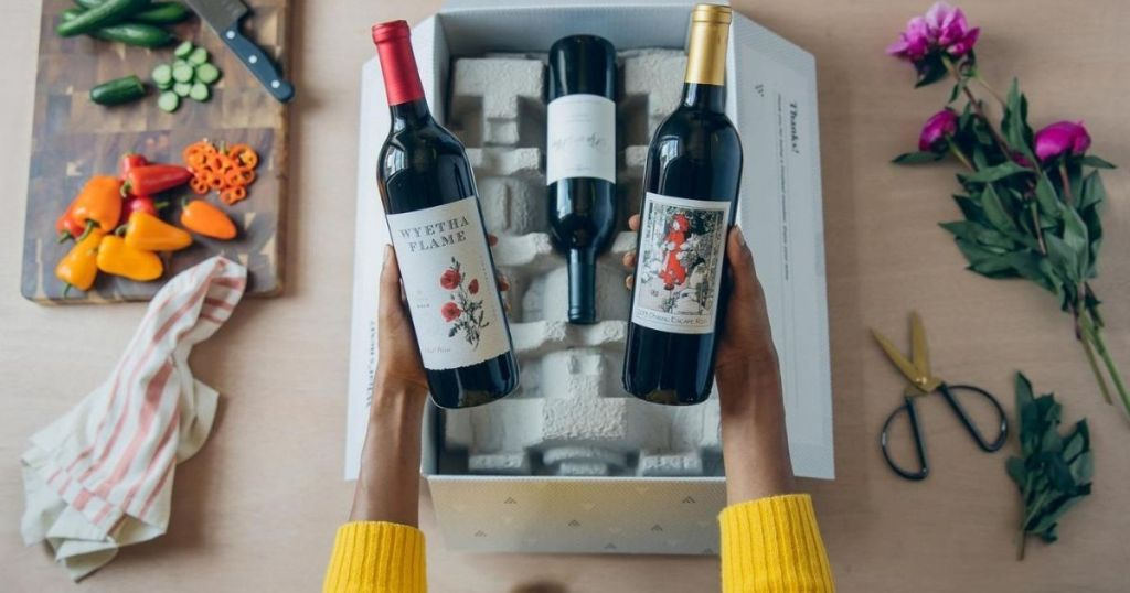 woman holding two bottles of wine up that she pulled out of a box of delivered wine