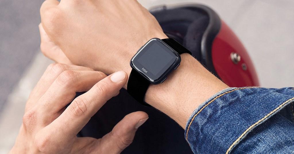 person wearing a black fitbit versa smartwatch on their wrist